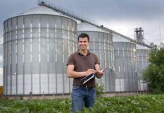 Farmer in front of grain silo Stock Photo