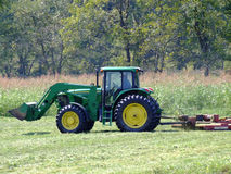 Farmer with Frontloader and Bush-Hog on his Tractor. Farmer mowing hay in field Royalty Free Stock Image