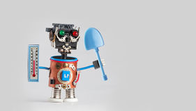 Farmer gardener robot with thermometer blue shovel in hands. Agriculture seasonal concept, funny toy character ready for Royalty Free Stock Images