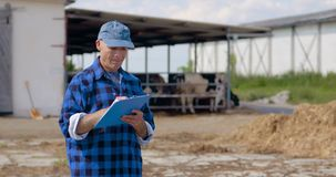 Farmer gesturing while writing on clipboard against barn. Lockdown shot of mature male farmer gesturing while writing on clipboard against barn. Agriculture stock video footage