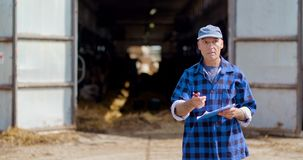 Farmer gesturing while writing on clipboard against barn. Lockdown shot of mature male farmer gesturing while writing on clipboard against barn. Agriculture stock footage