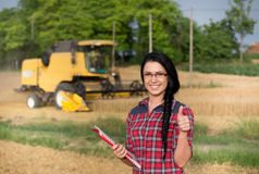 Farmer girl on field with combine harvester Royalty Free Stock Images