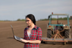 Farmer girl with laptop in field with tractor Royalty Free Stock Image