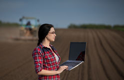 Farmer girl with laptop in field with tractor Stock Photos