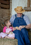 Farmer with granddaughter and kittens Royalty Free Stock Images