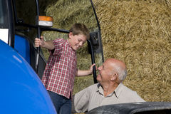 Farmer and grandson near tractor and hay Stock Images