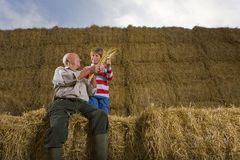 Farmer and grandson sitting on stack of hay bales Royalty Free Stock Image