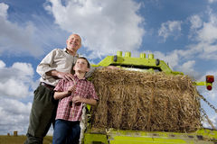 Farmer and grandson standing near machinery and straw bale Stock Photography
