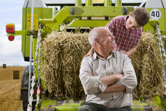 Farmer and grandson on tractor with straw Stock Images