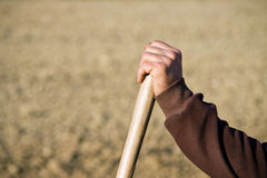 Farmer hand resting on wooden shovel or rake grip Stock Photos