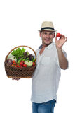 Farmer with harvest treats tomato in hand Royalty Free Stock Photography