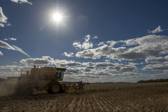 A farmer harvests a broadacre paddock of wheat. Stock Image