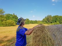 A farmer in a hat stands at a stack of fresh hay. A farmer in a hat looking in the field with stacks of fresh hay after harvesting wheat stock photography