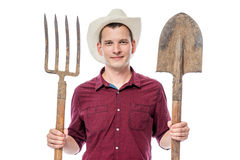 Farmer in hat with pitchforks and shovel Royalty Free Stock Photography