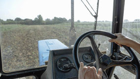 Farmer in hat, sits inside in the tractor cabin, rides on the field with plow. Closeup hands of farmer, sits inside in the tractor cabin, rides on the field Stock Photos