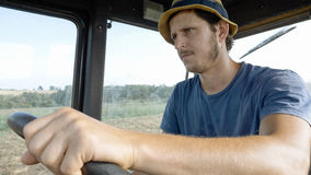 Farmer in hat, sits inside in the tractor cabin, rides on the field with plow. Portrait of young farmer in hat, sits inside in the tractor cabin, rides on the Stock Photography