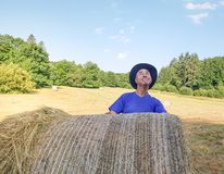 A farmer in a hat stands at a stack of fresh hay. After harvesting wheat and look sky stock photo