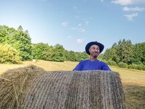 A farmer in a hat stands at a stack of fresh hay. After harvesting wheat . he is proud royalty free stock images