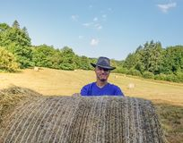 A farmer in a hat stands at a stack of fresh hay. After harvesting wheat . he is proud stock images
