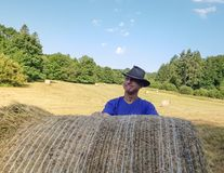 A farmer in a hat stands at a stack of fresh hay. After harvesting wheat . he is proud royalty free stock photography