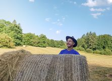 A farmer in a hat stands at a stack of fresh hay. After harvesting wheat and smile royalty free stock images