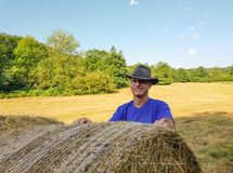 A farmer in a hat stands at a stack of fresh hay. After harvesting wheat and smile stock image