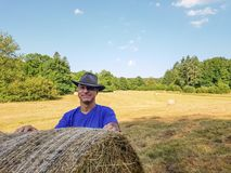 A farmer in a hat stands at a stack of fresh hay. After harvesting wheat and smile royalty free stock photography