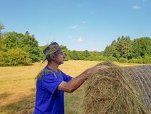 A farmer in a hat stands at a stack of fresh hay. A farmer in a hat looking in the field with stacks of fresh hay after harvesting wheat stock images