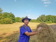 A farmer in a hat stands at a stack of fresh hay. A tired farmer in a hat stands at a stack of fresh hay after harvesting wheat and smile stock photos