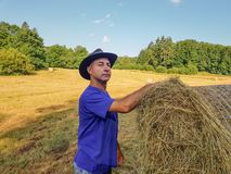 A farmer in a hat stands at a stack of fresh hay. A farmer, tired and proud of his work, stands around a stack of freshly harvested hay royalty free stock images