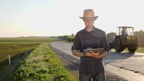 Farmer in a hat uses a digital tablet while standing on the road. A young farmer in a hat uses a digital tablet while standing on the road between the fields. In stock video footage