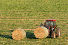 Farmer and hay bales. Farmer moving fresh bales of hay with his tractor royalty free stock photography