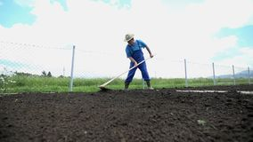 Farmer with hay hat using the rake on his garden stock footage