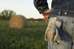 Farmer and Hay Stack. A farmer stands in a field in front of a hay bail Stock Photo