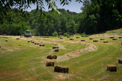 Farmer Haying Field. A farmer square bales his field with tractor and baler stock photography