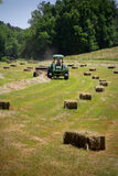 Farmer Haying Field. A farmer square bales his field with tractor and baler stock photos