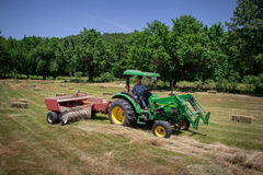 Farmer Haying Field. A farmer square bales his field with tractor and baler stock image