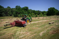Farmer Haying Field. A farmer square bales his field with tractor and baler royalty free stock photo