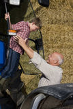 Farmer helping grandson down from tractor Royalty Free Stock Photos