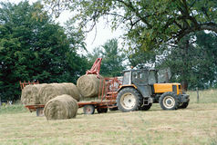 Farmer on his tractor picking up haystacks in Savoy, France Royalty Free Stock Images