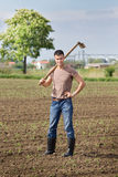 Farmer with hoe in corn field Stock Images