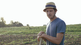 Farmer with hoe is resting while removes weeds in corn field at organic farm. Potrait of caucasian farmer in hat with hoe is resting and looking at camera while Stock Image