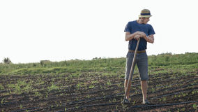 Farmer with hoe is resting while removes weeds in corn field at organic farm. Potrait of caucasian farmer in hat with hoe is resting and while removes weeds in Stock Photos