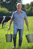 Farmer holding buckets Stock Image