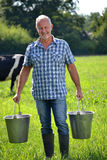 Farmer holding buckets Stock Images