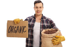 Farmer holding burlap sack with coffee and sign that says organi Stock Photo