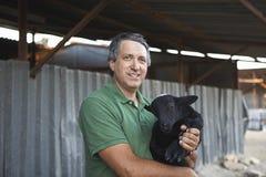 Farmer Holding Goat Stock Image