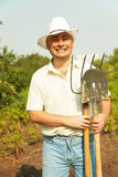 Farmer holding pitchfork and spade stock photo