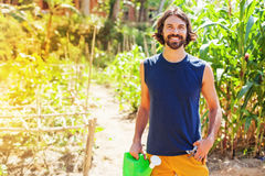 Farmer holding a watering can in a garden Stock Image