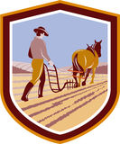Farmer and Horse Plowing Farm Field Crest Retro. Illustration of farmer and horse plowing farm field viewed from back set inside crest shield done in retro style Stock Photo